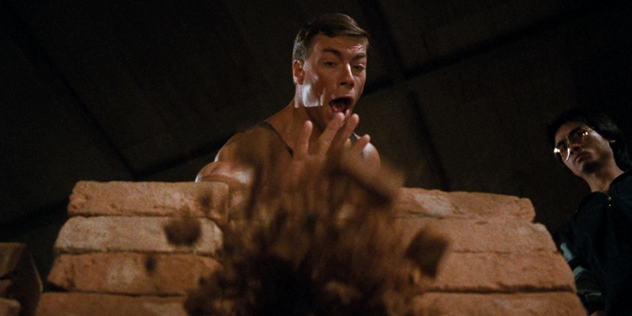 Jean-Claude Van Damme uses his IT prowess to explode a specific brick, which he is certain won't hit back (image property of Warner Bros.)